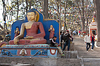 Kathmandu, Nepal.  Statues of the Buddha Guard the Stairs Leading to the Swayambhunath Temple Hilltop.  Prayer Flags Hang Over the Route.