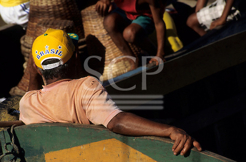 Amazon, Brazil. Man wearing a Brasil cap sitting in boat with kids and baskets in boat behind.