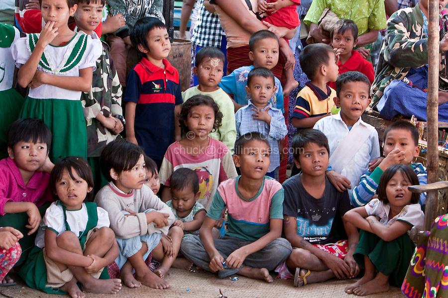 Myanmar, Burma.  Bagan.  Burmese Children Watching a Dancer at a Nat Pwe Celebration, thanking the spirits for a year of good fortune.