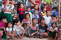 Myanmar, Burma.  Bagan.  Burmese Children Watching a Dancer at a Nat Pwe Celebration, thanking the spirits for a year of good fortune.