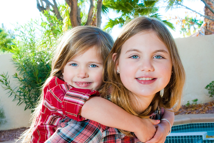 Two sisters pose for a portrait outdoors.