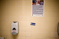 A Mitt Romney campaign sticker hangs on the wall of a bathroom at a Romney town hall campaign event at McKelvie Intermediate School in Bedford, New Hampshire, on Jan. 9, 2012.  Romney is seeking the 2012 Republican presidential nomination.