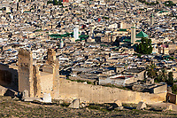 Fes, Morocco.  Old City (Fes El-Bali), Kairaouine Mosque (in center, with white minaret), Zawiya of Moulay Idris (on right, with tiled minaret).  Remains of old city wall, seen from the hill of the Merenid Tombs.