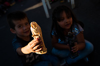 A Mexican boy, sitting next to his sister, shows a figurine of Santa Muerte (Holy Death) during a religious pilgrimage in Tepito, a rough district of Mexico City, Mexico, 1 April 2018. The religious cult of Santa Muerte is a fusion of Aztec death worship rituals and Catholic beliefs. Born in lower-class neighborhoods of Mexico City, it has always been closely associated with crime. In the past decades, original Santa Muerte followers, such as prostitutes, pickpockets and street drug traffickers, have merged with thousands of ordinary Mexican Catholics. The Holy Death veneration, offering a spiritual way out of hardship in modern society, rapidly expanded. Although the Catholic Church still considers Santa Muerte followers the devil worshippers, on the first day of every month, crowds of Santa Muerte believers fill the streets of Tepito. Holding statues of Holy Death clothed in a long robe, they pray for healing, protection, money or any other favor in life.