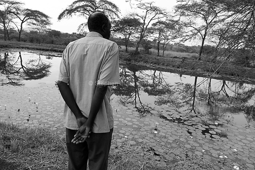 Empowering Victims of War- Mr. Opobbo, the farmÕs manager, surveys the onsite pond. The pond supplies the farm with water, as well as supplies the residents of the farm with protein rich fish. Canaan Family Farm lends land to displaced people from the Northern conflict to have them learn the benefits of work and empowerment. Rwakayata, Masindi, Uganda, Africa. December 2005 © Stephen Blake Farrington