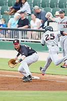 Danny Hayes (32) of the Kannapolis Intimidators stretches for a throw as Gregory Lorenzo (25) of the Delmarva Shorebirds lunges for the first base bag at CMC-NorthEast Stadium on July 3, 2014 in Kannapolis, North Carolina.  The Shorebirds defeated the Intimidators 6-5. (Brian Westerholt/Four Seam Images)