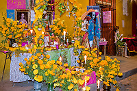 Oaxaca; Mexico; North America.  Day of the Dead Celebrations.  Skeleton Mannequins Invite Customers into Shop Selling Souvenirs, Toys, and Jewelry.  An Altar to the Owner's Parents sits to the left of the door, decorated with marigolds, the traditional flower used to honor the ancestors.