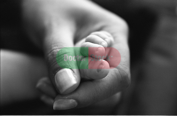 mother's hand around newborn baby foot