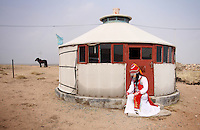 A tourist dressed in traditional Mongolian dress sits outside of a yurt on the Xilamuren grasslands that dominate the north of the Inner Mongolian capital, Hohhot. The grasslands have increasingly come under threat in recent years as drought, climate change and desertification increase and degrade these once fertile lands. Overgrazing is also contributing the deterioration of this unique ecosystem.