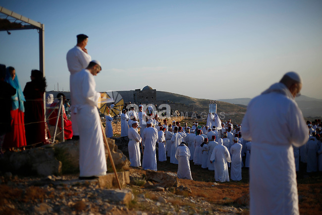 Members of the Samaritan community pray at sunrise during a religious service marking the end of their Passover holiday atop Mount Gerizim, above the West Bank city of Nablus, 02 May 2021. According to tradition, the Samaritans are descendants of the Jews who were not deported when the Assyrians conquered Israel in 722 BC. The small community numbers about 810 people, half of them live in a village at Mount Gerizim, near the Palestinian city of Nablus, and the rest in Holon near Tel Aviv in Israel. Photo by Shadi Jarar'ah