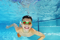 Boy swimming underwater in pool.