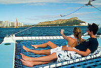 A couple lounges on the netting of a catamaran with Waikiki and Diamond Head in the background.