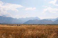 A view over the dry and desolate plain. The Kastrat Shkrel mountains in the background. On the road between Shkodra and the border to Montenegro. Albania, Balkan, Europe.