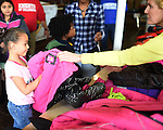 WATERBURY, CT- 27 November 2015-112715EC03--   Jalyn Rodriguez, 6, tries on a coat Friday at St. Anne's in Waterbury. It was one of six locations where Knights of Columbus distributed free coats for children. The Waterbury spot had nearly 500 coats to give away Friday. 2,000 coats were distributed througout the state. Erin Covey Republican-American.