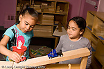 Education Preschool 4-5 year olds two girls playing with toy cars vehicles and ramp made of wooden blocks horizontal