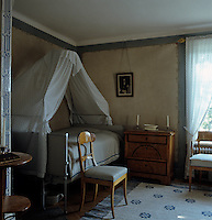 A guest room features a delicate hand-painted wallpaper and is furnished with Biedermeier furniture and an 18th century folding canopied campaign bed