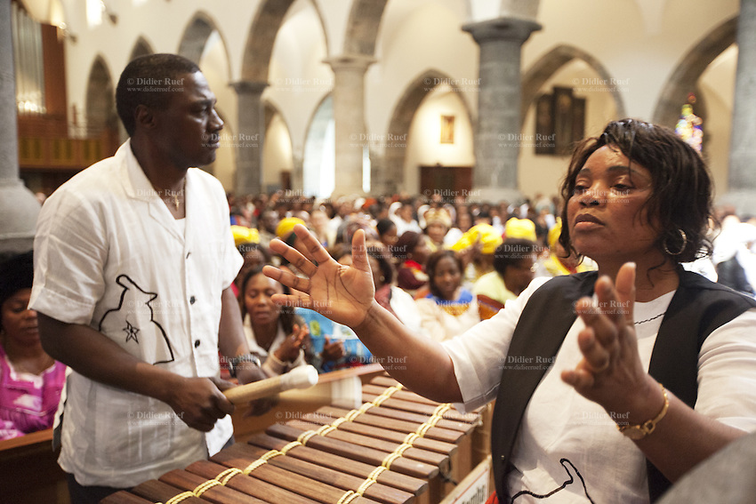 Switzerland. Canton Valais. St-Maurice. Africa Saints Pilgrimage (Pèlerinage aux Saints d'Afrique). Religious <br /> ceremony in St-Maurice's abbey. African women and men gather for a catholic mass. They sing, dance and listen to music payed by drums and balafon instruments. The balafon (bala, balaphone) is a resonated frame, wooden keyed percussion idiophone of West Africa. The balafon is part of the idiophone family of tuned percussion instruments. Sound is produced by striking the tuned keys with two padded sticks. 2.06.13 © 2013 Didier Ruef