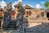 Bali, Indonesia.  Family Hindu Temple inside Family Residential Compound.  Klungkung, Semarapura.  Nagas (serpents) guard entrance to steps; behind them dwarapalas (guardians) flank both sides of entrance.  Elevated shrines to the ancestors are along the back wall.