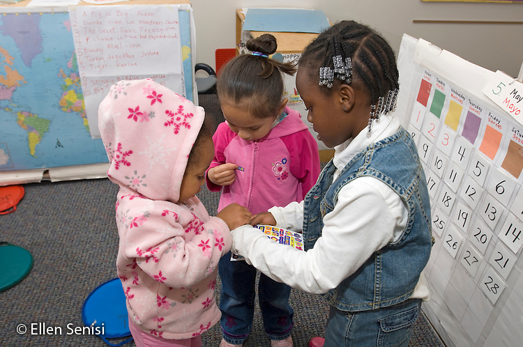 MR / Washington D.C..Rosemount Headstart - Bilingual (English-Spanish) Early Childhood Program.(Pre-K Class).Girl (5, African-American) giving stickers to her friends (girl left: 3, African-American / Hispanic-American; Middle: 4, Salvadorian-American). .MR: Mit9, Fer4, Mar23.© Ellen B. Senisi