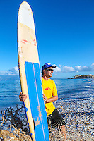 A surf instructor holds a surfboard at Ka'anapali Beach, Maui.