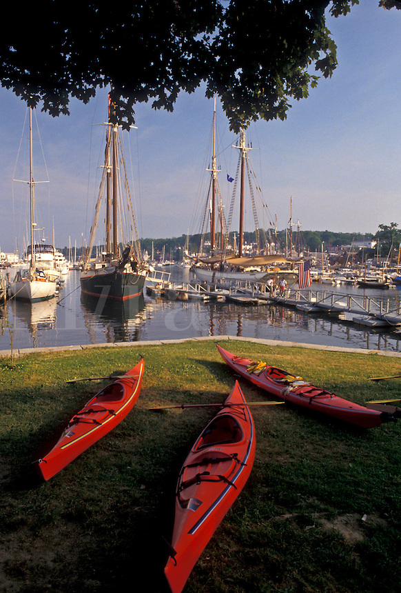 AJ4470, Camden, sea kayak, harbor, Maine, Atlantic Ocean, Red sea kayaks ready for renting on the lawn at the scenic harbor in the seaside town of Camden in the state of Maine.