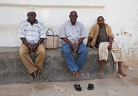 Stone Town, Zanzibar, Tanzania.  Three Men Sitting on a Baraza, a Stone Bench outside the door of many houses in Stone Town.