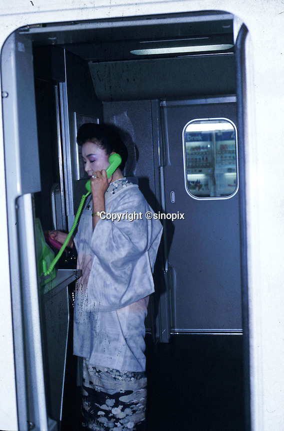 A woman wear traditional Japanese kimono talking on the phone in the train in Japan.