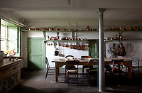 The green and white kitchen, its brass pots and pans neatly arranged on the shelves which run the length of the room