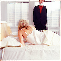 Woman in bed with man in background along windows<br />