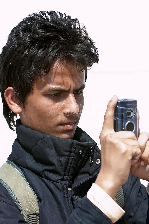 Bodhnath, Nepal.   Young Nepali Man at the Buddhist Stupa of Bodhnath, taking Picture with Cell Phone Camera.