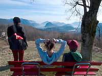 Switzerland. Canton Ticino. Monti di Bigorio. A mother and her children, her daughter Micaela and her son Nicola, take a rest and watch the landscape. Sunny day and blue sky. View on the Alps and the lake Lugano ( also called Lago Ceresio). Bigorio is located in the Capriasca valley. 11.03.12 © 2012 Didier Ruef