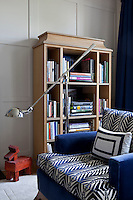 A blue and white patterned armchair and freestanding bookcase in grey-painted, wood-panelled living room