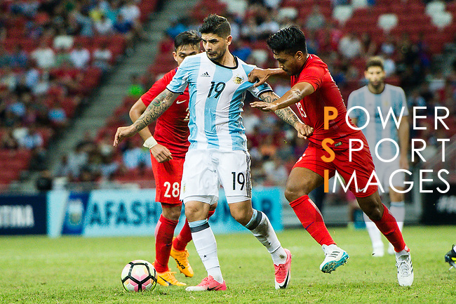 Ever Banega of Argentina (L) fights for the ball with Izzdin Shafiq of Singapore (R) during the International Test match between Argentina and Singapore at National Stadium on June 13, 2017 in Singapore. Photo by Marcio Rodrigo Machado / Power Sport Images