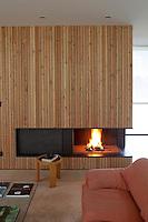 The glow of a fire in the contemporary fireplace warms the orange sofa in the living area