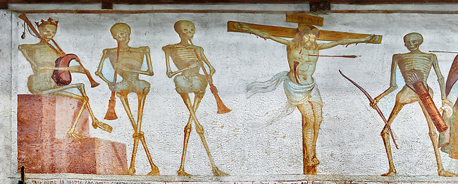 """Crucifiction fresco on the Church of San Vigilio in Pinzolo, part of its mural painting """"the Dance of Death"""" painted by Simone Baschenis of Averaria in1539, Pinzolo, Trentino, Italy.<br /> <br /> The mural continues for another 21 meters with a long procession with 40 figures. The Mural opens on its left with a skeleton on the throne, bearing a sceptre and the crown and playing a bagpipe. These skeletons are playing the music which is the backdrop to """"Dance of Death"""" ( Danza macabra ) and suggests that they are playing with our fate on earth.<br /> <br />  To the right of the skeletons playing music is a depiction of the crucification. Christ is depicted on the cross with an arrow in him that has been fired by a skeleton with a bow. This suggests that because Christ was a man he suffered the fate of death as we all will."""
