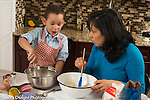 3 year old boy in kitchen at home with mother learning to cook baking, stirring ingredients in bowls