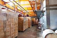 The vat room with stainless steel vats and wooden cases of wine.  Domaine Yves Cuilleron, Chavanay, Ampuis, Rhone, France, Europe
