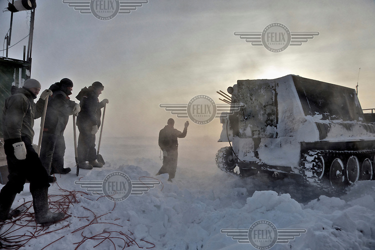 Workers signal a snow tank to reverse at a camp set up by oil and gas prospecting company Siesmorevzedka in the Arctic tundra. /Felix Features