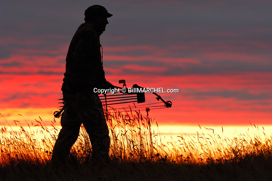 00105-039.17 Bowhunting (DIGITAL) Archer is silhouetted against colorful sky at the magic hour.  Color, drama.  H4R1