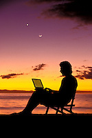 Man uses a laptop at the beach at sunset.
