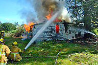 Firefighter trainees put multiple streams of water on a burning house as flames billow out  during a house training burn for the Goldridge Fire Academy Training Class.
