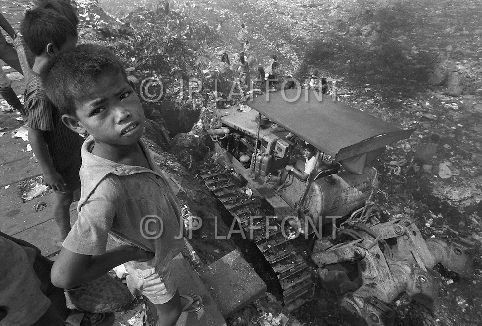 Children collect items for sale in a garbage dumb outside Manilla, Philippines - Child labor as seen around the world between 1979 and 1980 – Photographer Jean Pierre Laffont, touched by the suffering of child workers, chronicled their plight in 12 countries over the course of one year.  Laffont was awarded The World Press Award and Madeline Ross Award among many others for his work.