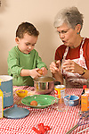3 year old boy cooking baking activity with grandmother Caucasian vertical breaking eggs into batter