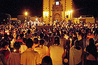 Devout ;CATHOLICS light candles during EASTER MASS at SAN ANTONIO CHURCH - SAN MIGUEL DE ALLENDE, MEXICO .