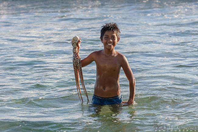 A young i-kiribati holding a freshly caught octopus.
