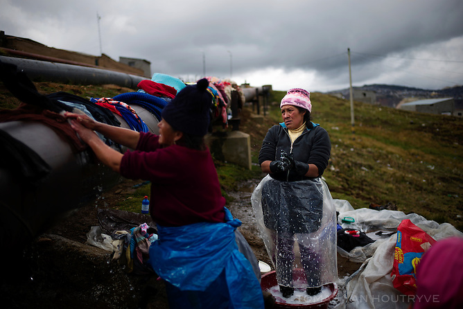 Women wash clothing with water taken from a hole in an industrial water pipeline used by the Volcan mining company in the Carlos Mariategui neighborhood of Cerro de Pasco, Peru. On the left is Abdona Taquiri de Vargas. On the right is Lucia Vilma Portal Gonzales.