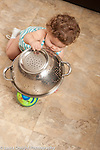 13 month old baby girl at home Piaget object permanence looking for and finding toy ball hidden under metal colander vertical