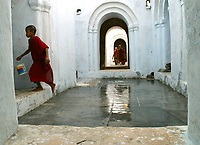 A young monk runs off after wetting down the monastery courtyard floor in central Myanmar (Burma).  02/12/05 © Julia Cumes / The Image Works