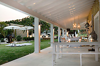 As dusk falls, candles are lit on the covered terrace where dainty chandeliers illuminate the beamed ceiling
