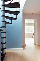 A minimalist hallway with a wooden floor and one blue and one pink painted wall. An open sliding door leads to a bedroom beyond. A spiral staircase leads up to a converted attic space.